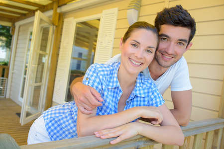 rented: Couple embracing on terrace of chalet Stock Photo