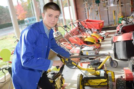 empleadas domesticas: Joven trabajador en la tienda de cortadora de césped Foto de archivo