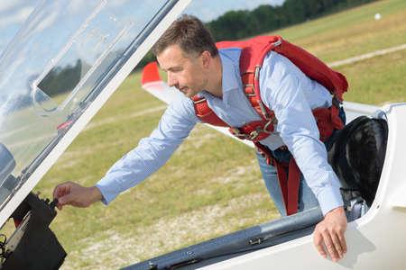 controls: Man adjusting controls on stationary aircraft
