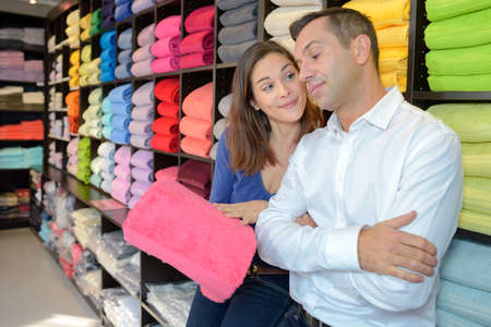 persuades: Woman trying to convince man to buy pink towel