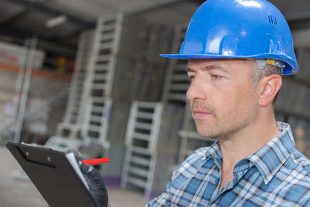 writing materials: Man in hardhat making notes Stock Photo