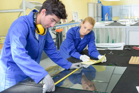 pane: Young man measuring pane of glass