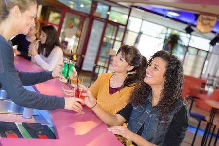 hotel bar: friends being served drinks in hotel bar