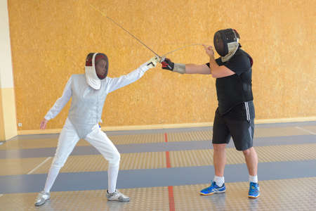 fencing foil: People pacticing the sport of fencing