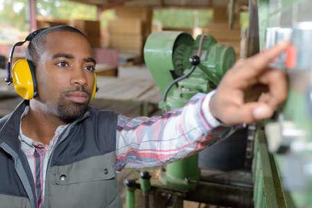 fabricator: worker adjusting the machine Stock Photo