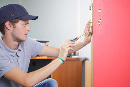 Man fitting lock into interior fire door Stock Photo