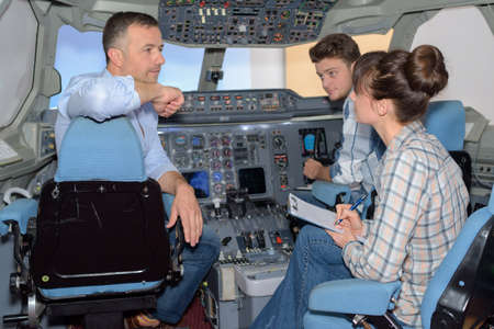 Young people questioning man in cockpit of aircraft