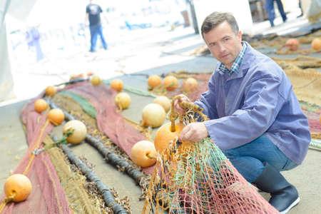 untangle: Man organising fishing nets Stock Photo