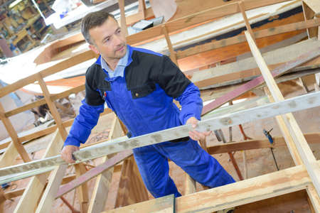 erecting: Man erecting timber frame