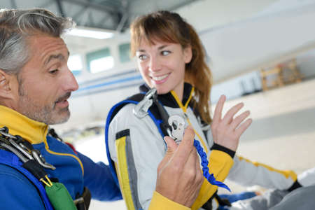 costume  sponsored: Man and woman attaching straps to their jumpsuits Stock Photo