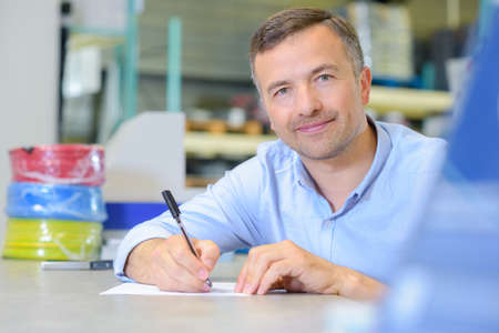 Man sat at table with pen and paper Stock Photo