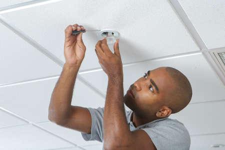 fixing: fixing a light fixture Stock Photo