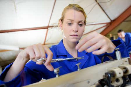 snip: Lady cutting thread on sewing machine Stock Photo