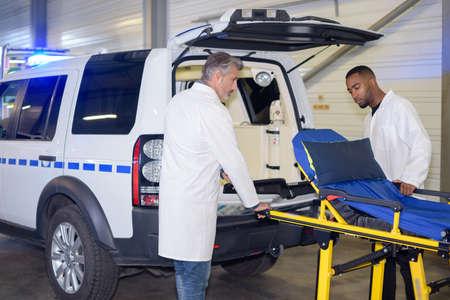 wheeling: Paramedics wheeling stretcher towards ambulance