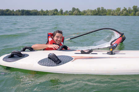 Man in water with windsurfing board