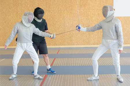 fencers: three fencers on a practice