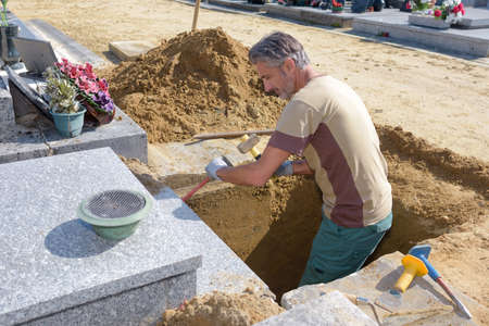 chr: Man in grave using hammer and chisel Stock Photo
