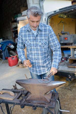farrier: Farrier using anvil Stock Photo