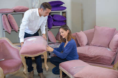 stool: Couple looking at upholstered stool Stock Photo