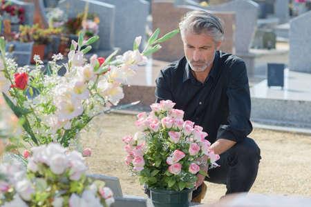 黒服の男がお墓の前でひざまずいた