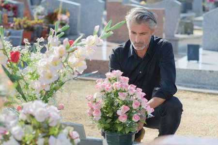 Man in black knelt at grave Stock Photo