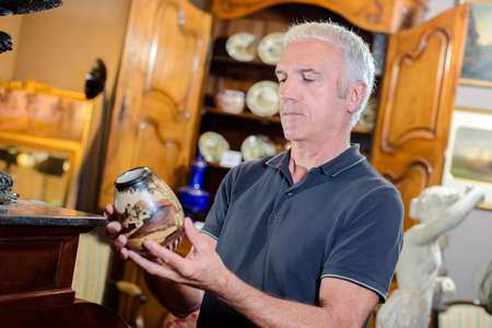 Man looking at antique vase Stock Photo