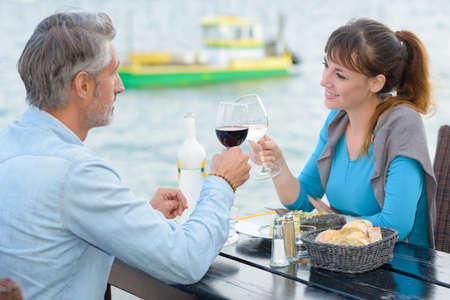 Couple toasting at riverside restaurant