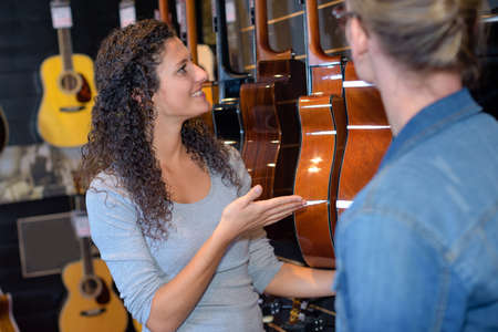 sell: Lady presenting guitars in shop Stock Photo