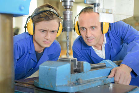industrial noise: Young man watching engineer use bench drill
