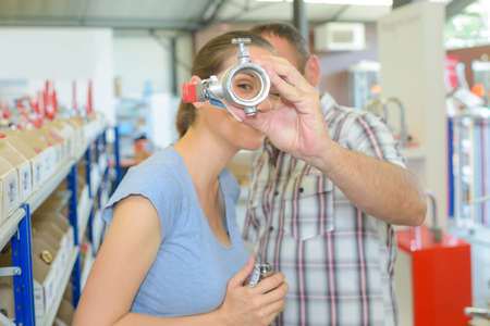 fitting in: Woman looking through hole in pipe fitting