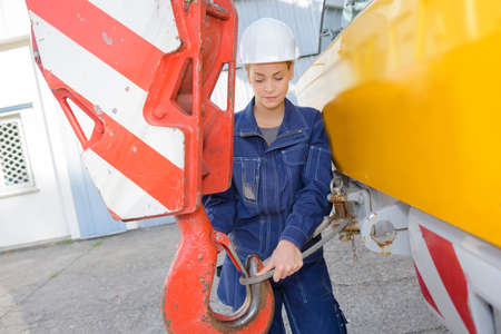 attaching: Woman attaching cable to winch of crane Stock Photo