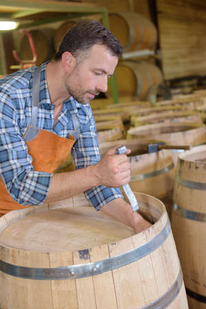 cooper: wood barrels production cooper using hammer and tools in workshop