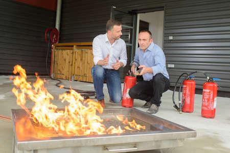 extinguishers: Men training with fire extinguishers