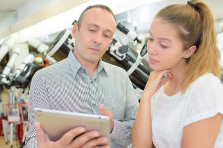 Man and young lady looking at tablet Stock Photo