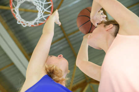 Upward view of woman aiming for basketball net