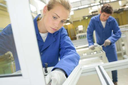 Young people working in window factory Foto de archivo