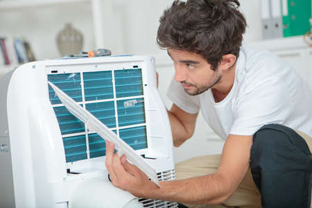 dismantle: Man working on air conditioning unit