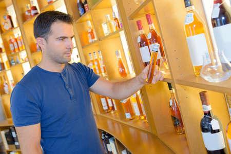 temptation: Man choosing bottle from shelf in store