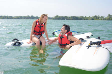 lifejacket: Couple in water with windsurfing boards