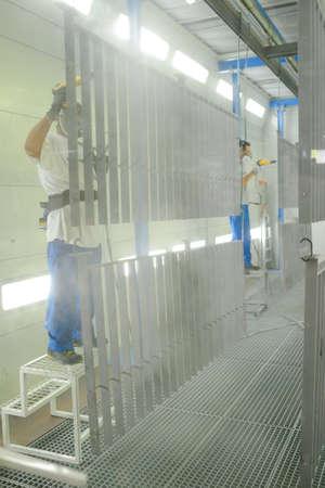Men cleaning metal grid