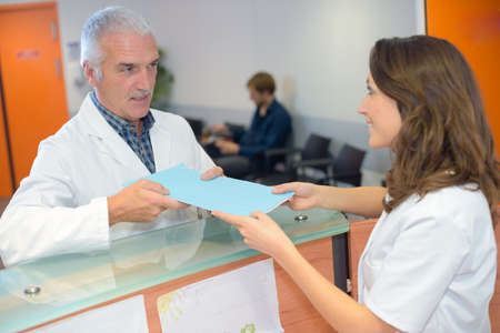 clerical: Doctor handing file to receptionist Stock Photo