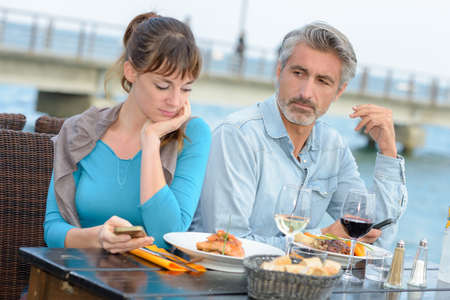 disgruntled: Couple having meal, woman using smartphone