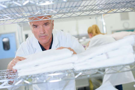 laundrette: Senior man stacking clean laundry on shelf Stock Photo