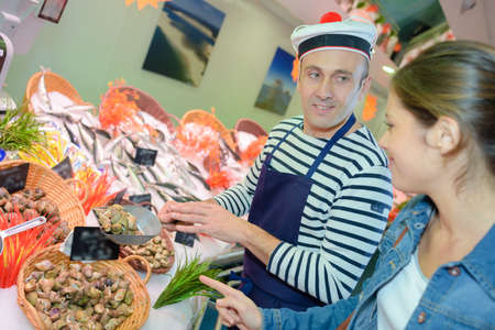 merchandiser: seafood vendor wearing a french hat Stock Photo