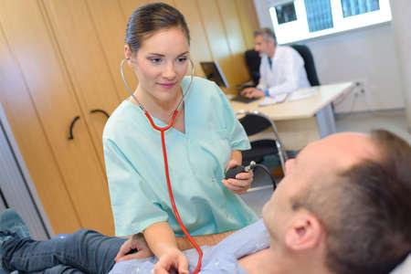 estetoscopio corazon: Nurse listening to patients heart with stethoscope Foto de archivo