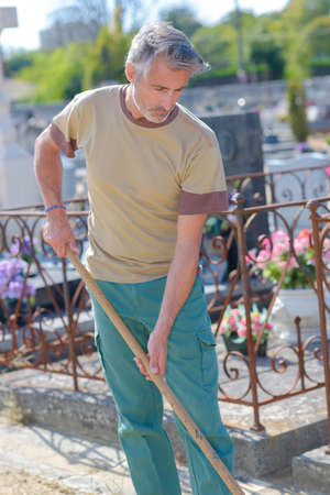 cemetary: caretaker raking in the cemetary
