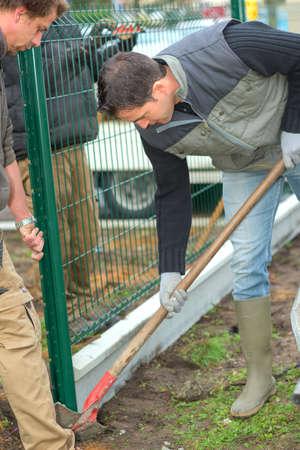 putting up: Gardeners putting up a perimeter
