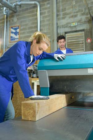 guiding: Worker guiding wooden beam through machine