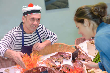 fishmonger: Fishmonger serving customer Stock Photo