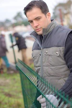 picket green: Workman fitting outdoor fencing